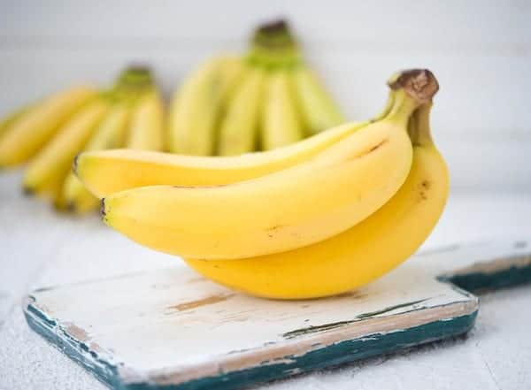 bunch of bananas on a board with other bunches in the back ground