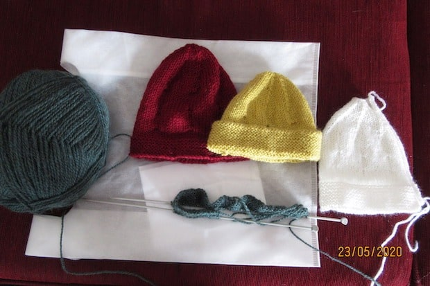 baby beanies with ball of wool and knitting